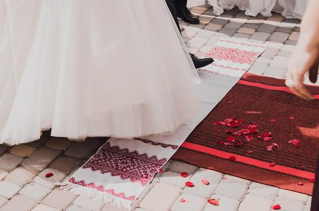A noiva e o noivo dão um passo nas toalhas nacionais brancas