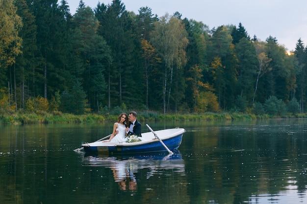 A noiva e o noivo em um barco a remo no lago ao pôr do sol