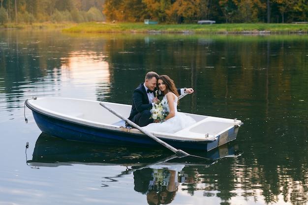 A noiva e o noivo em um barco a remo no lago