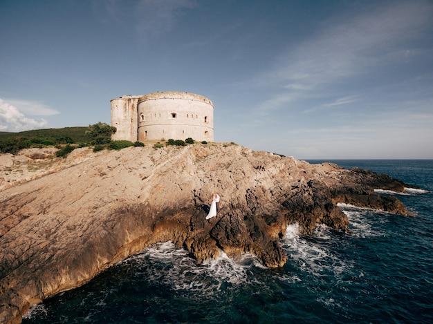 A noiva e o noivo estão abraçados e de mãos dadas na costa rochosa perto da fortaleza de arza
