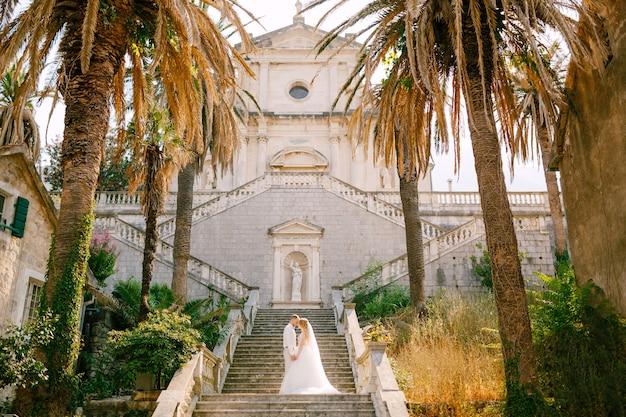 A noiva e o noivo estão abraçados e de mãos dadas na escada