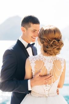 A noiva e o noivo estão abraçados e sorrindo no cais perto do mar, close-up