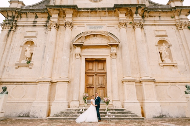 A noiva e o noivo estão abraçados perto da porta na escada do presépio da virgem abençoada