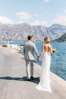A noiva e o noivo estão caminhando ao longo do cais na baía de kotor de mãos dadas, a noiva está