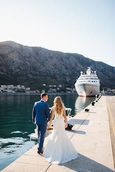 A noiva e o noivo estão caminhando de mãos dadas ao longo do cais, perto da vista traseira do navio turístico branco