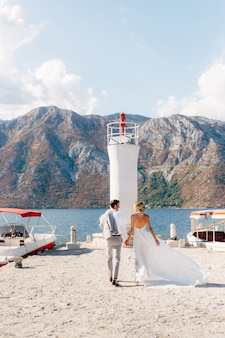 A noiva e o noivo estão de mãos dadas ao longo do cais do farol na baía de kotor