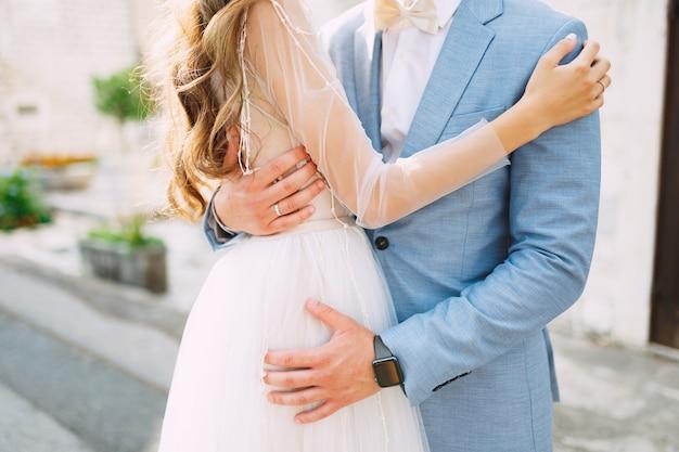 A noiva e o noivo estão se abraçando ternamente na rua da cidade velha de perast closeup