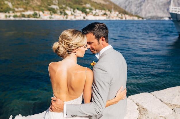 A noiva e o noivo estão sentados abraçados no cais da baía de kotor, na frente deles é o