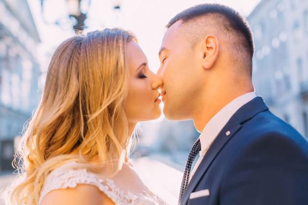 A noiva e o noivo fecharam os olhos e beijaram