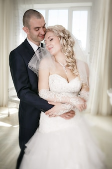 A noiva e o noivo felizes no casamento andam na janela da frente