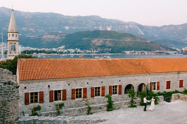 A noiva e o noivo giram, de mãos dadas, perto da igreja na cidade velha de budva