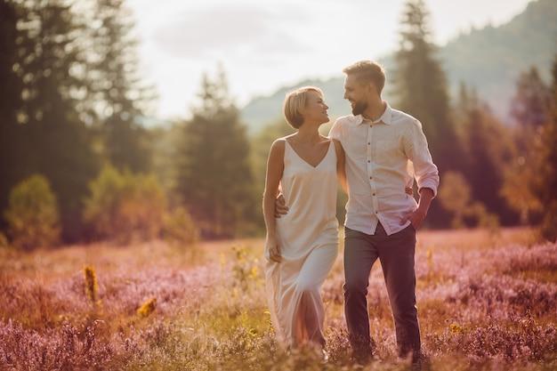A noiva e o noivo mantêm-se mutuamente as mãos girando no campo