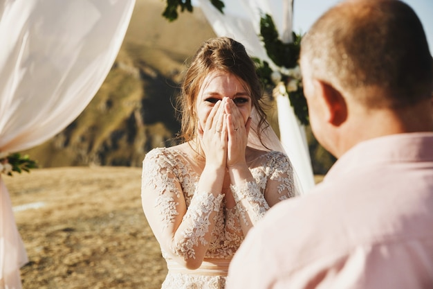 A noiva e o noivo parecem adoráveis durante a cerimônia de casamento no topo da montanha em algum lugar da geórgia