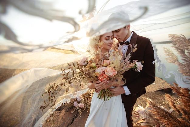 A noiva e o noivo perto da decoração do casamento em uma cerimônia em um penhasco de rocha perto da água ao pôr do sol. véu voando com o vento