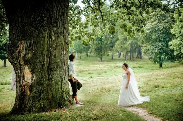 A noiva e o noivo perto de madeira velha no verão