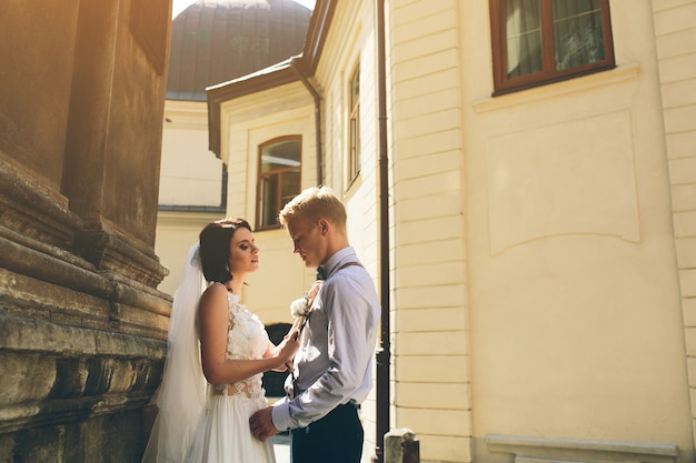 A noiva e o noivo posando na velha rua