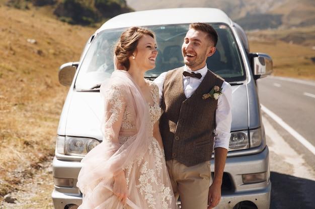 A noiva e o noivo riem de pé diante de um antigo ônibus em algum lugar nas montanhas georgianas