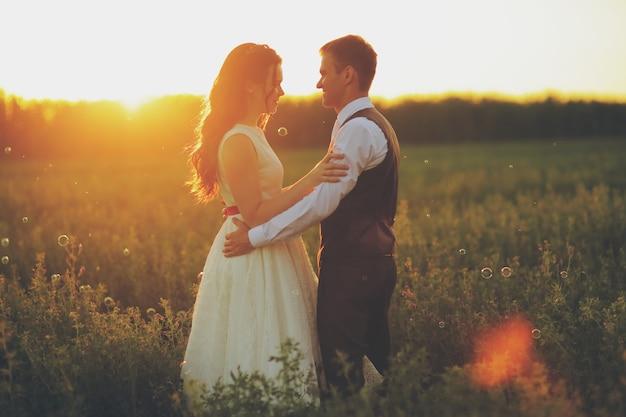 A noiva e o noivo se abraçam no parque ao pôr do sol casamento. conceito feliz.