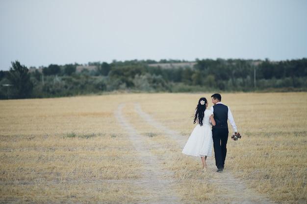 A noiva e o noivo se dão as mãos, se abraçam e caminham no parque.