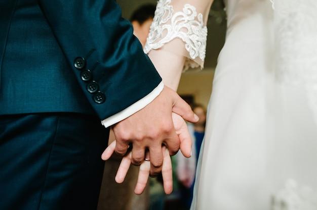 A noiva e o noivo segurando nas mãos e em pé na cerimônia de casamento ao ar livre no quintal da natureza.