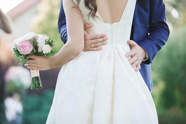 A noiva e o noivo segurando um buquê de casamento