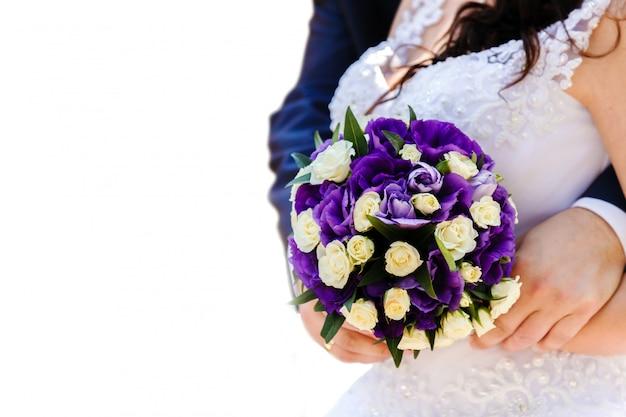 A noiva e o noivo segurando um buquê de flores brancas e roxas