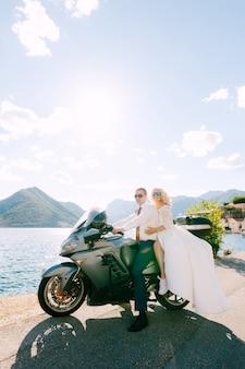 A noiva e o noivo sentam em uma motocicleta no cais e a noiva abraça o noivo