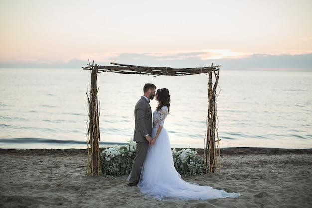 A noiva e o noivo sob arco na praia