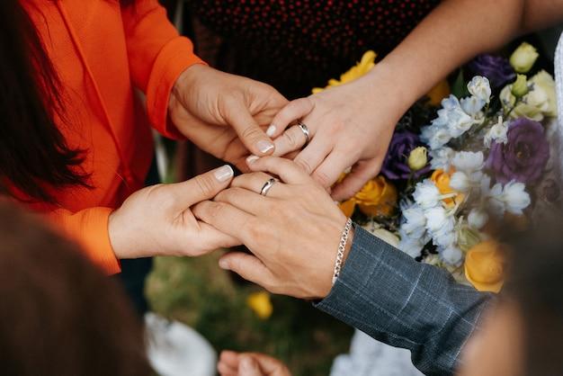 A noiva e o noivo, ternamente, dão as mãos entre eles, amor e relacionamentos.