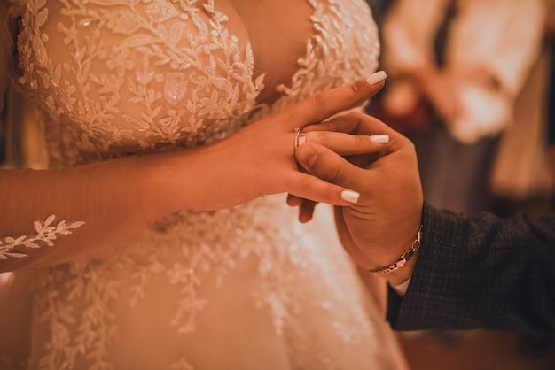 A noiva e o noivo trocam alianças