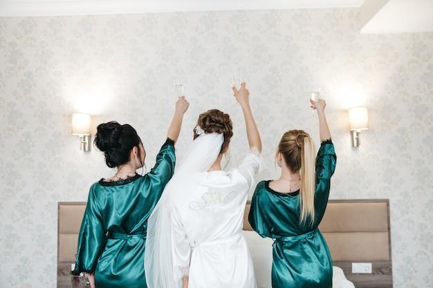 A noiva e suas amigas celebram a manhã do dia do casamento
