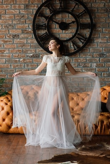 A noiva é uma morena de aparência europeia. penteado e maquiagem de casamento. boudoir no hotel.