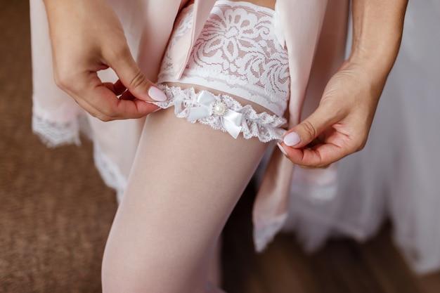 A noiva em branco coloca uma atadura openwork bonita em uma perna elegante. conceito de casamento