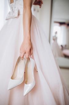 A noiva em seu vestido de noiva tem seus elegantes sapatos bege nas mãos.