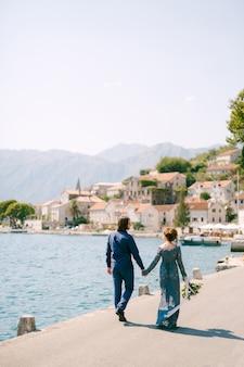 A noiva em um elegante vestido azul e o noivo caminham ao longo do cais de mãos dadas perto da cidade velha de perast, vista traseira. foto de alta qualidade