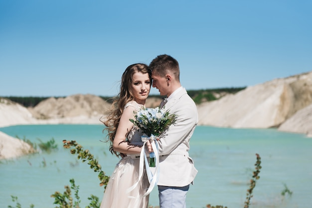 A noiva em um lindo vestido, abraçando o noivo em um terno claro perto do lago. casal de noivos em pé em uma colina de areia ao ar livre. uma história de amor romântica. água azul-azulada no horizonte.