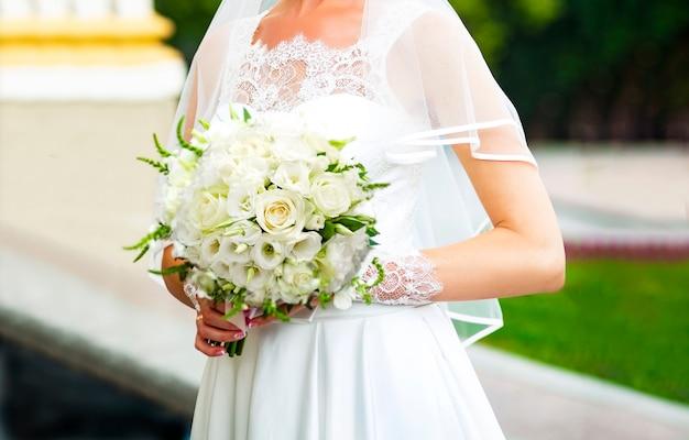 A noiva em um lindo vestido branco tem nas mãos um lindo buquê de rosas brancas e eustomas