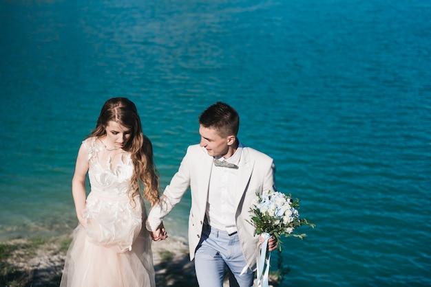 A noiva em um lindo vestido de mãos dadas com o noivo em um terno claro contra o céu azul e a água azul. casal de noivos em pé em uma colina de areia ao ar livre. uma história de amor romântica.