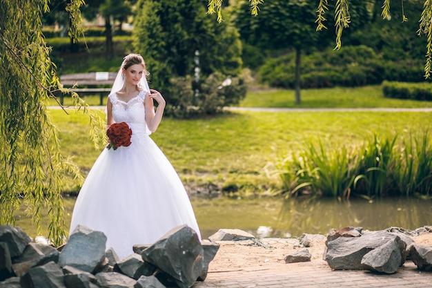 A noiva em um vestido branco e com um buquê de rosas vermelhas nas mãos dela caminha em um parque da cidade em um dia quente de outono. retrato de casamento
