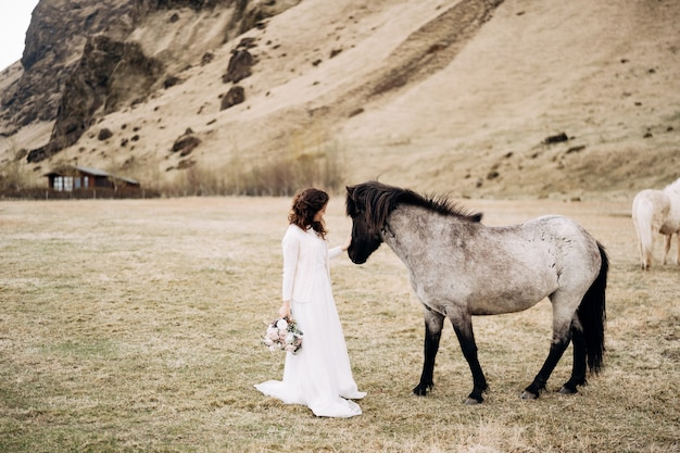 A noiva em um vestido branco e um buquê nas mãos acariciando um cavalo com uma crina preta no rosto