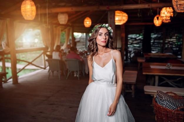 A noiva em um vestido branco e uma coroa de flores está no restaurante