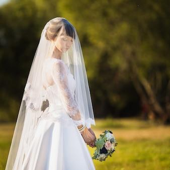 A noiva em um vestido branco no fundo da natureza. fotografia de casamento.