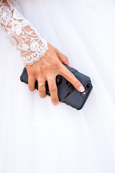 A noiva em um vestido branco tem um smartphone na mão.
