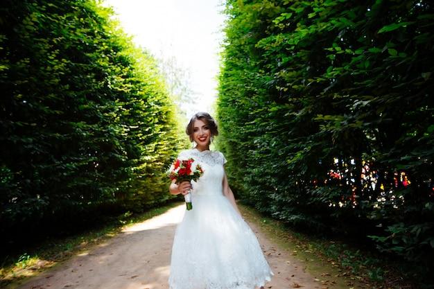 A noiva em um vestido de noiva branco detém um buquê em um fundo de parque verde