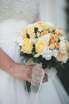 A noiva em um vestido de noiva branco elegante está segurando um lindo buquê de flores diferentes e folhas verdes. tema casamento