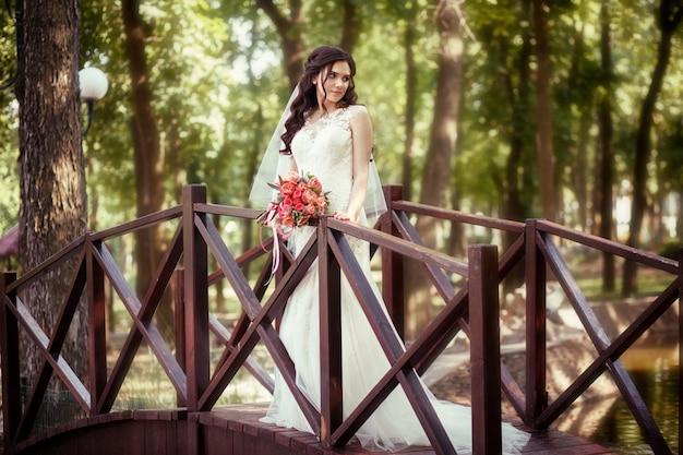 A noiva em um vestido de noiva branco fica no contexto de uma cachoeira artificial em um parque da cidade