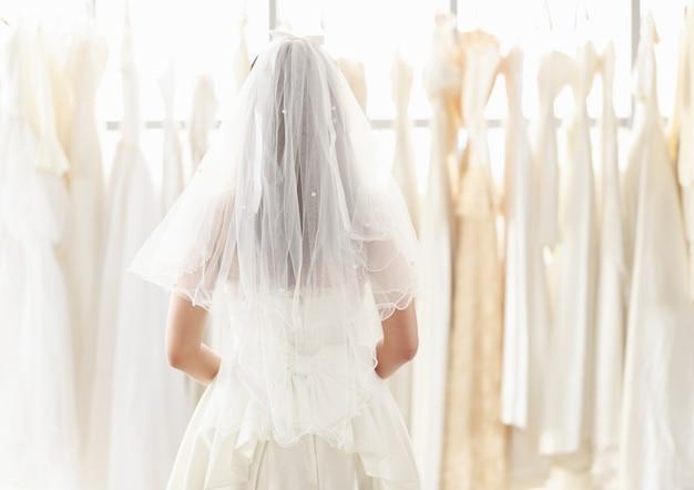 A noiva em um vestido de noiva de renda branca em pé para trás e olhar para o vestido de noiva no provador. mulher escolhendo muitos vestidos de noiva na loja.