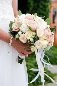 A noiva em um vestido de noiva elegante branco está segurando um lindo buquê de flores diferentes e folhas verdes. tema do casamento. foco seletivo.