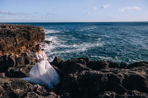 A noiva em um vestido de noiva estiloso fechou os olhos e cruzou os braços