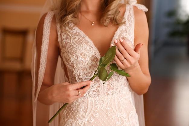 A noiva em um vestido de renda branca tem uma rosa de casamento nas mãos.
